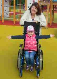 Jess in a wheelchair with arms outstretched