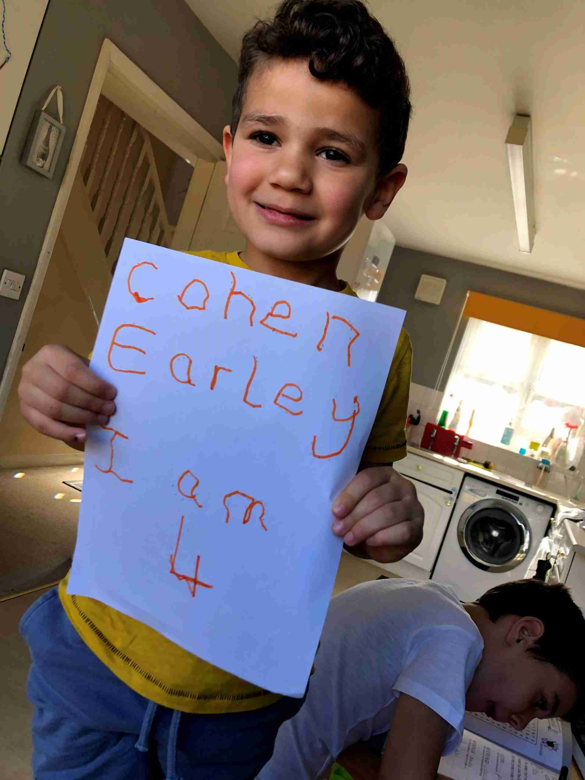Cohen holding up sign saying I Am Four