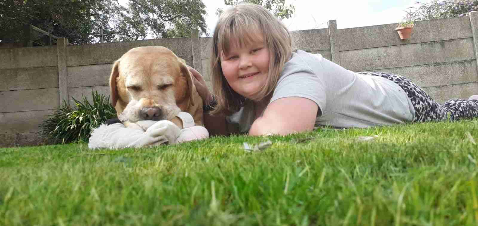 Jess lying on the grass with a dog